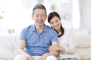 ソファーに座りカメラ目線で笑う夫婦の写真素材 [FYI02969453]