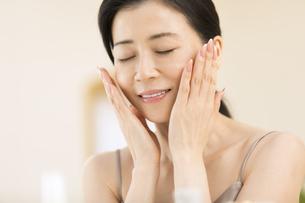頬に両手を添えて目を瞑る女性の写真素材 [FYI02969459]