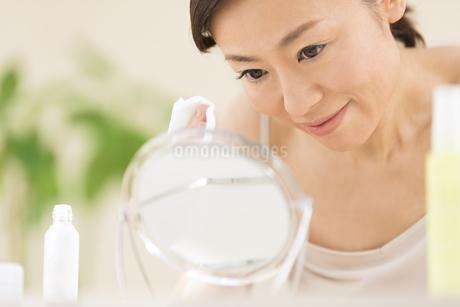 手にコットンを持ちスキンケアをする女性の写真素材 [FYI02969461]