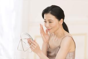 鏡の前でスキンケアをする女性の写真素材 [FYI02969463]