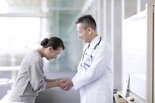 手を握り感謝をする患者と男性医師の写真素材 [FYI02969465]