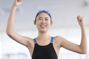 ガッツポーズで喜ぶ水着の女子学生の写真素材 [FYI02969467]