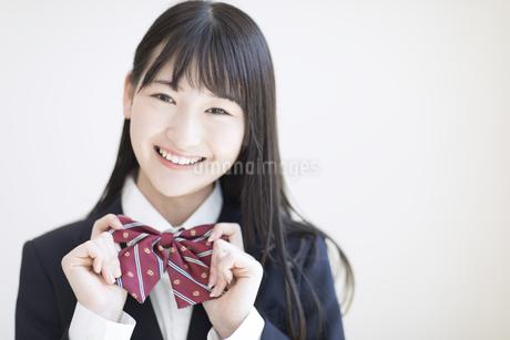 リボンを持ちカメラ目線で笑顔の女子高校生の写真素材 [FYI02969470]