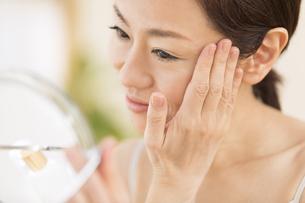 鏡の前でスキンケアをする女性の写真素材 [FYI02969472]