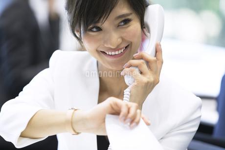 時間を気にしながら電話をするビジネス女性の写真素材 [FYI02969473]