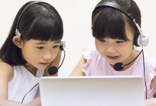 インカムを付けてパソコンを見る女の子2人の写真素材 [FYI02969474]