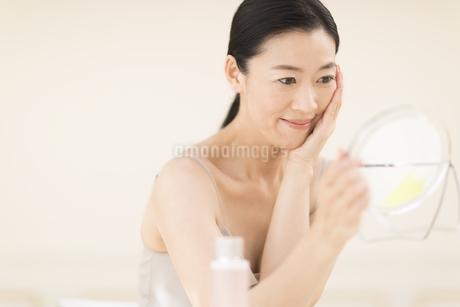 鏡の前でスキンケアをする女性の写真素材 [FYI02969479]