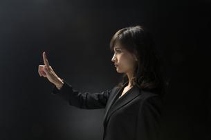 指を指すポーズをとるビジネス女性の横顔の写真素材 [FYI02969480]