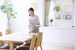 お皿をテーブルに置く女性の写真素材 [FYI02969484]