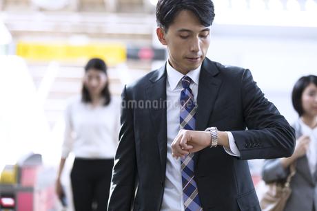 駅の改札付近で時計を見るビジネス男性の写真素材 [FYI02969488]