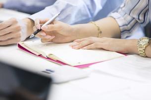 手帳に記入するビジネス女性の手元の写真素材 [FYI02969494]