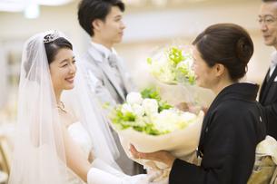 両親に花束を贈る新郎新婦の写真素材 [FYI02969495]