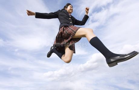青空をバックにジャンプをする女子高校生の写真素材 [FYI02969499]