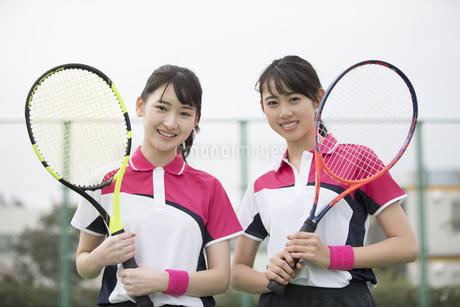 テニスラケットを持ちカメラ目線の女子学生たちの写真素材 [FYI02969503]