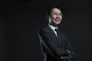 腕を組み微笑むビジネス男性の写真素材 [FYI02969504]