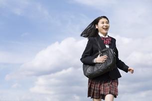 青空をバックに走る女子高校生の写真素材 [FYI02969508]