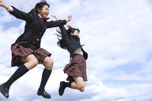 青空をバックにジャンプをする女子高校生たちの写真素材 [FYI02969515]