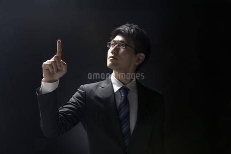 指を指すポーズをとるビジネス男性の写真素材 [FYI02969516]