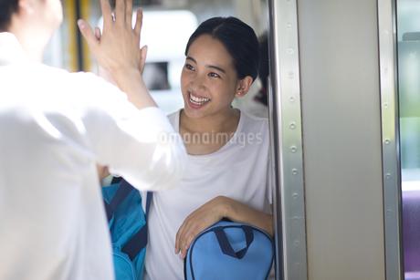 電車の入り口で会話をする男女の写真素材 [FYI02969519]