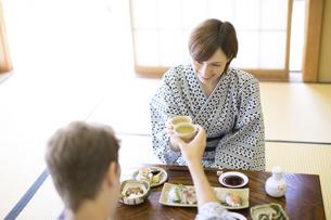 日本酒で乾杯をする男女の外国人観光客の写真素材 [FYI02969524]