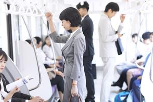 電車でつり革を持って立つビジネス女性の写真素材 [FYI02969529]