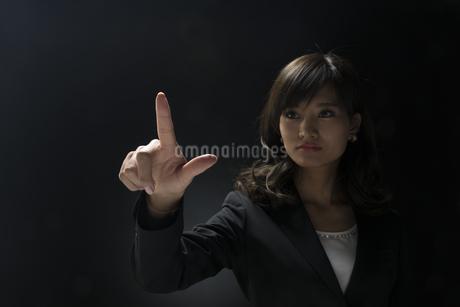 指を指すポーズをとるビジネス女性の写真素材 [FYI02969530]