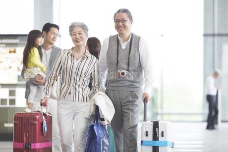 キャリーバッグを引いて歩くシニア夫婦の写真素材 [FYI02969538]