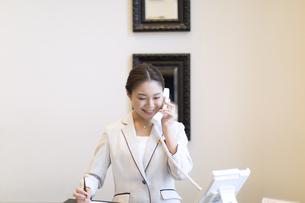 電話対応をするコンシェルジュの女性の写真素材 [FYI02969548]
