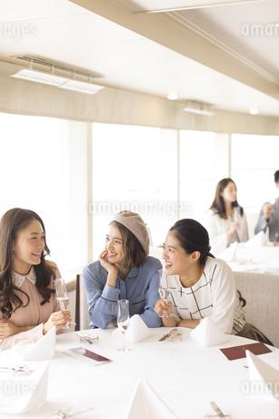 シャンパンを持ち会話をする3人の女性の写真素材 [FYI02969552]