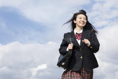 青空をバックに走る女子高校生の写真素材 [FYI02969560]