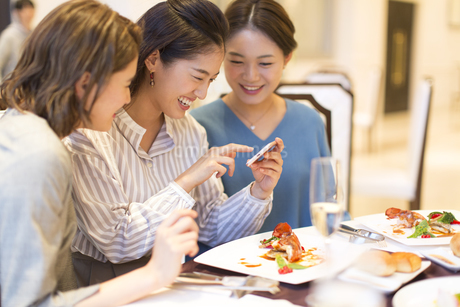 スマートフォンで料理を撮る3人の女性の写真素材 [FYI02969563]