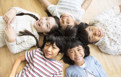 床に寝転んで笑う子供たちの写真素材 [FYI02969564]