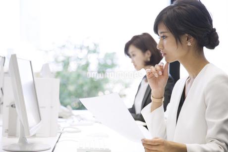 資料を持ちパソコンを見るビジネス女性の写真素材 [FYI02969571]