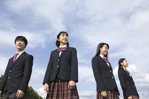 青空をバックに立つ高校生たちの写真素材 [FYI02969575]