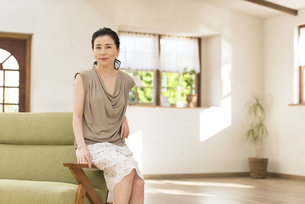 ソファーの肘掛けに腰掛ける女性の写真素材 [FYI02969576]