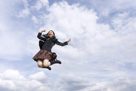 青空をバックにジャンプをする女子高校生の写真素材 [FYI02969577]