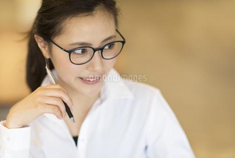 ペンを持ち横を見るビジネス女性の写真素材 [FYI02969578]