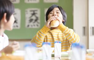 給食のパンを口に頬張る男の子の写真素材 [FYI02969581]