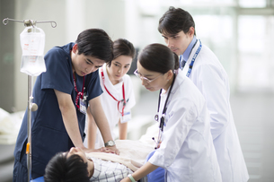 救急患者に心臓マッサージを行う医師と看護師の写真素材 [FYI02969591]