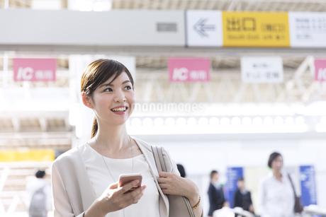 駅でスマホを持ちながら周りを見るビジネス女性の写真素材 [FYI02969595]