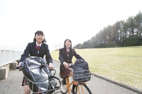 自転車で通学をする女子高校生たちの写真素材 [FYI02969596]