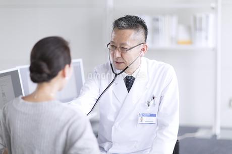 患者に聴診器をあてる男性医師の写真素材 [FYI02969597]