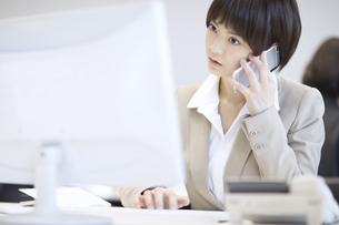 パソコンを見てスマートフォンで通話するビジネス女性の写真素材 [FYI02969602]