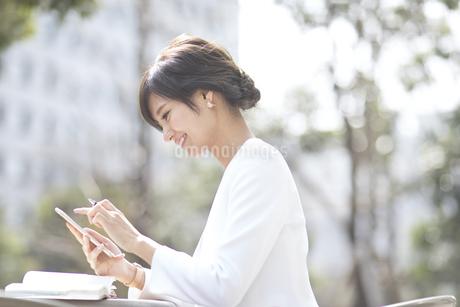 スマートフォンを操作するビジネス女性の写真素材 [FYI02969604]
