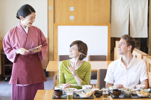 追加料理を注文する外国人の男女の写真素材 [FYI02969613]