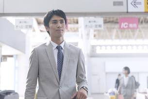 駅で遠くを見ながら歩くビジネス男性の写真素材 [FYI02969614]