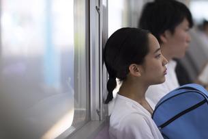 電車の座席に座り遠くを見つめる女性の写真素材 [FYI02969617]