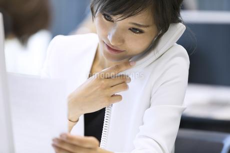 資料を見ながら電話をするビジネス女性の写真素材 [FYI02969618]