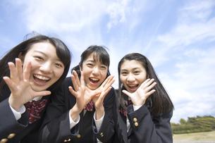 青空をバックにカメラに声をかける女子高校生たちの写真素材 [FYI02969626]