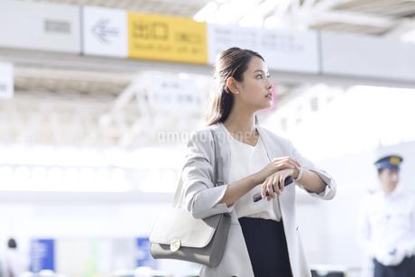 駅で時計を触りながら周りを見るビジネス女性の写真素材 [FYI02969630]